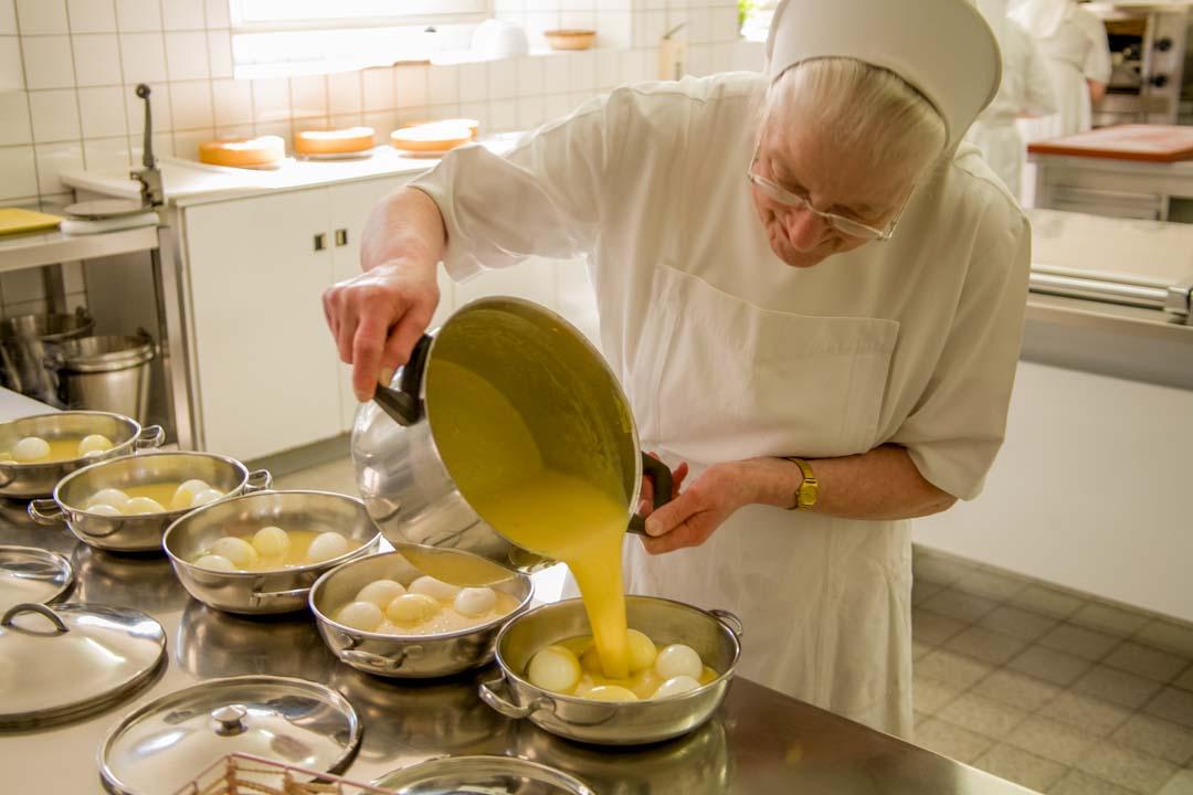 Eine Schwester beim Portionieren des Mittagessens
