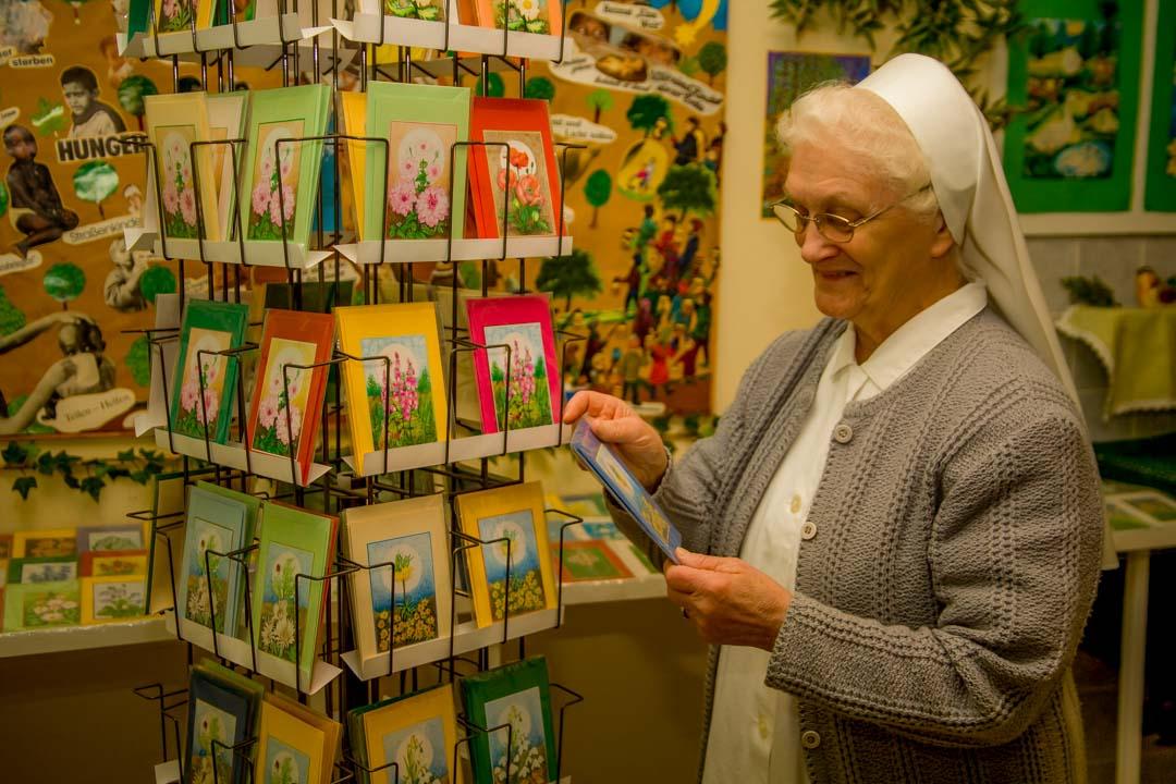 Schwester steht vor Ihren handgemalten Kunstpostkarten