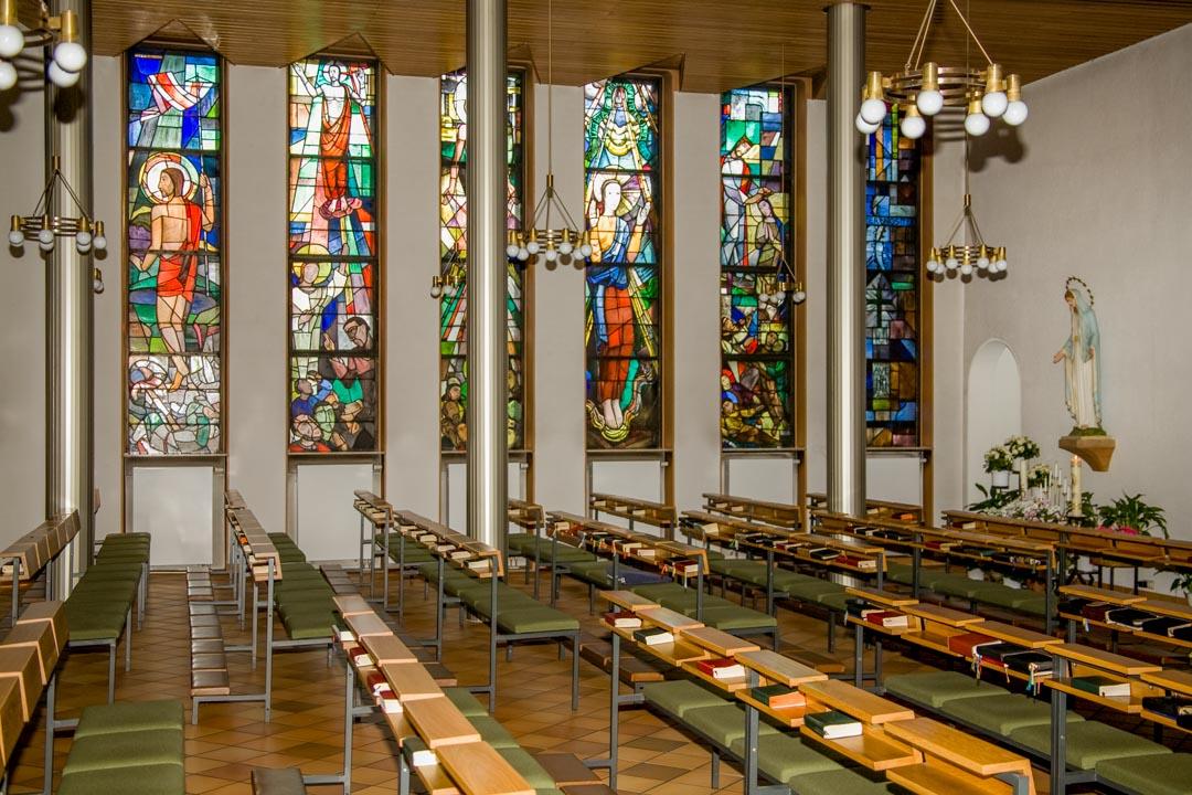 Das Kirchenschiff mit Bankreihen, Säulen und Bleiglasfenster zur Ostseite. Auf einem Podest steht eine Marienstatur