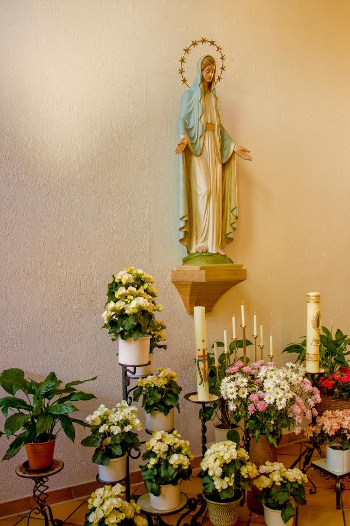Ausschnitt der Klosterkapelle mit Marienstatur, Blumenschmuck und Kerzen