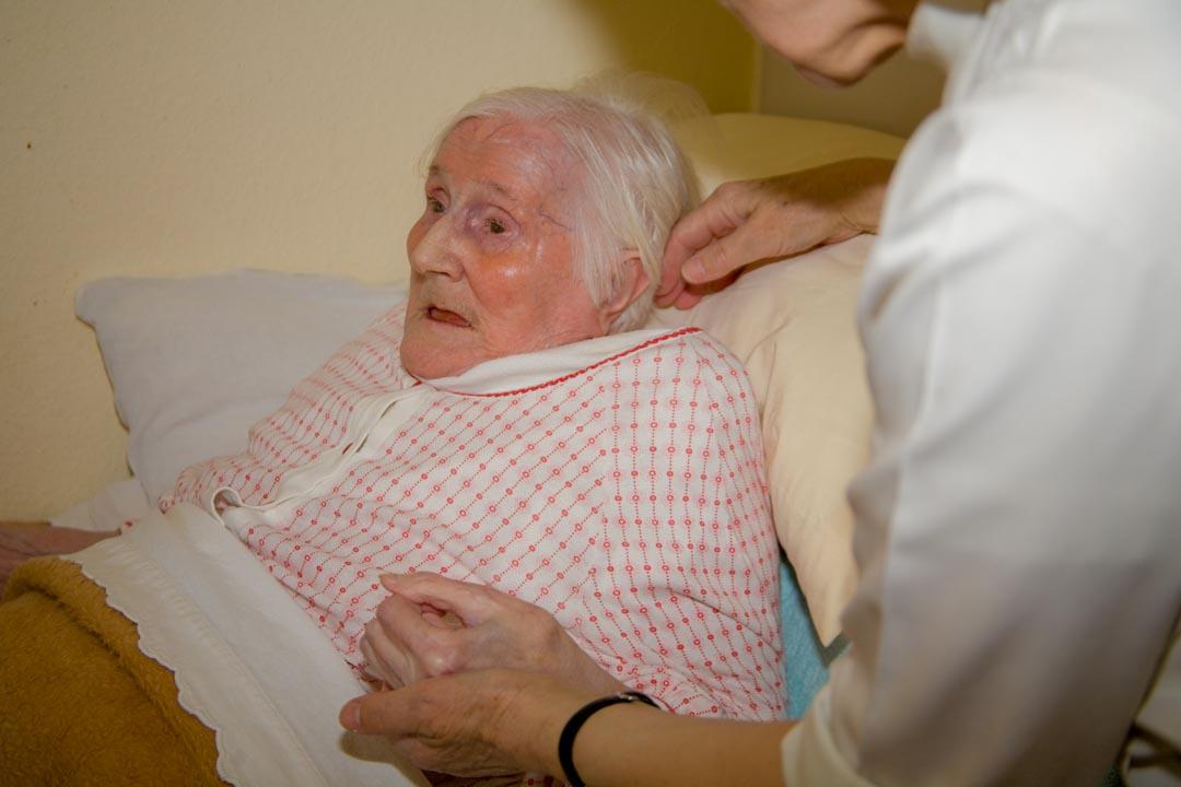 Schwester auf der Pflegestation im Gespräch mit einer Mitschwester im Rollstuhl die auf Hilfe angewiesen ist