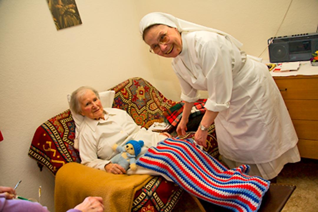 Schwester im Pflegebereich bei der Versorgung einer hilfsbedürftigen Mitschwester