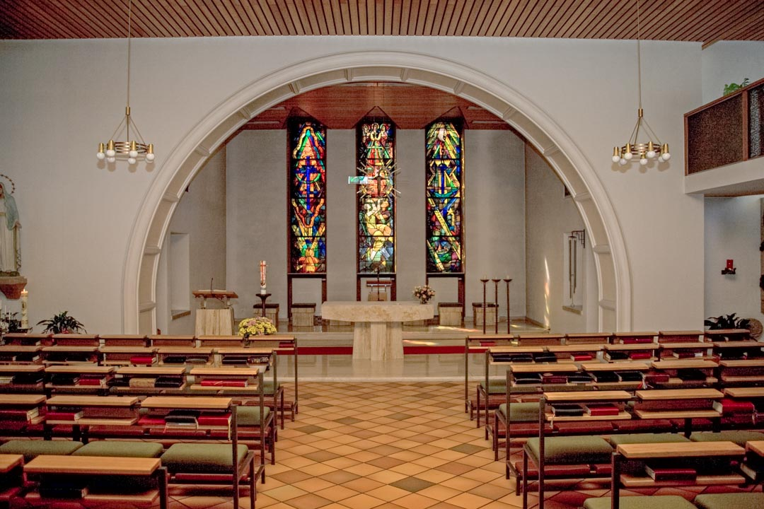 Die Klosterkapelle mit Blick auf den Altarraum mit Rundbogen und Bleiglasfenster.
