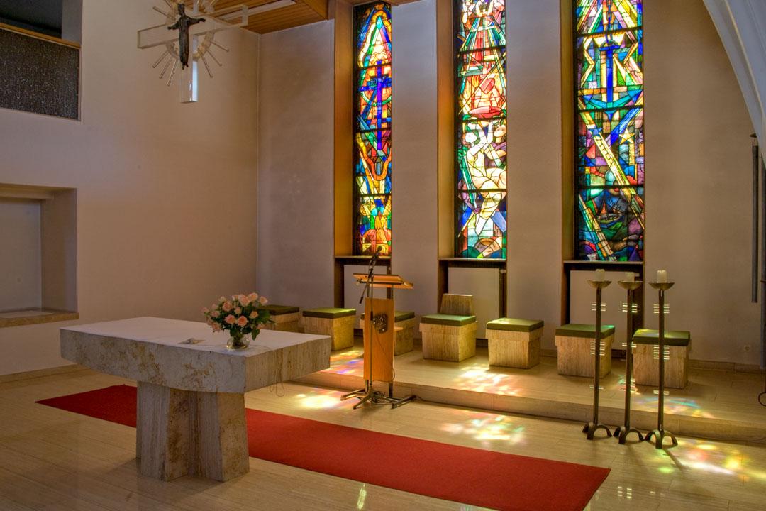 Chorbereich in der Kapelle. Das Abendlicht durchflutet die farbigen Fenster