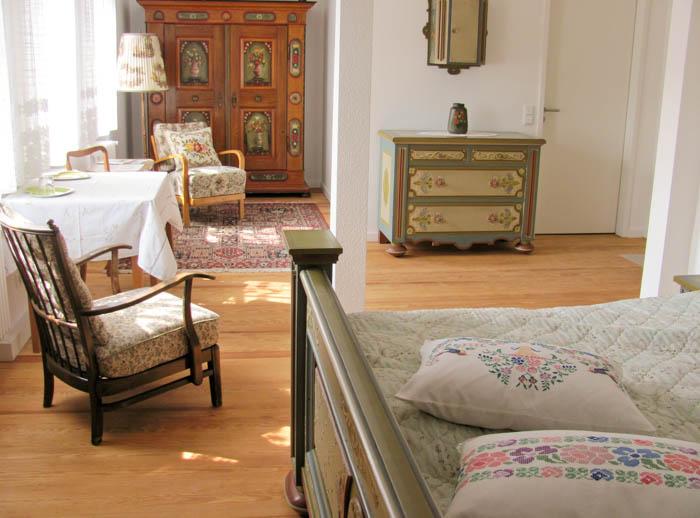 Doppelzimmer im Gästebereich mit aus Holz gearbeitetem Doppelbett, Sitzecke und Schränken, die mit Bauernmalerei verziert sind