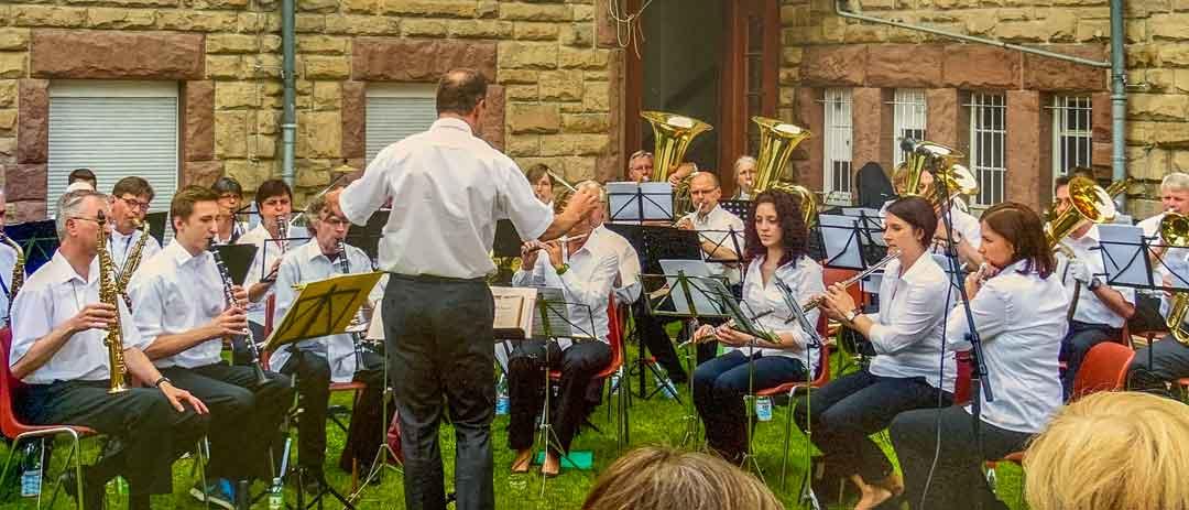 Die Stadtkapelle Heppenheim spielt im Klostergarten | Orchester mit Dirigent davor