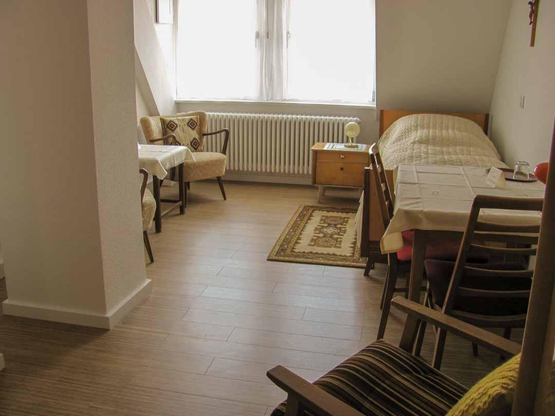 Einzelzimmer für Gäste mit Bett und Nachttisch, Eßtisch und Stühlen, Sitzecke mit zwei Sesseln und WC.