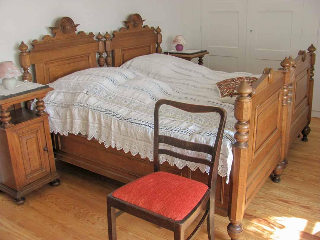 Doppelzimmer im Gästebereich mit aus Holz gearbeitetem Doppelbett und Nachttischen.