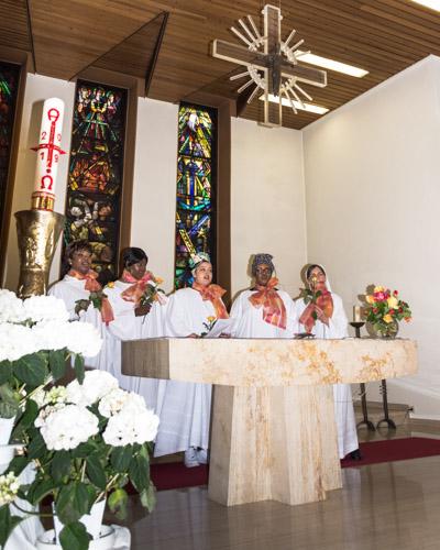 Die fünf Frauen des Gospelchors in weißen Gewändern und orangefarbenen Halstüchern, stehend hinter dem Marmoraltar und dem von der Decke herabhängenden Kreuz. Seitlich befindet sich die Osterkerze und Blumenschmuck.