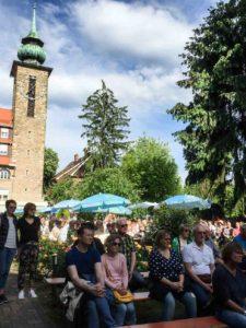 Die Zuhörer des Serenadenkonzerts sitzen auf Bänken im Klostergarten, es sind Sonnenschirme aufgestellt, im hinteren Teil des Bildes befindet sich der Kirchturm un die angrenzende Metzendorf Villa. Die Bäume des Klostergartens spenden zusätzlich Schatten.