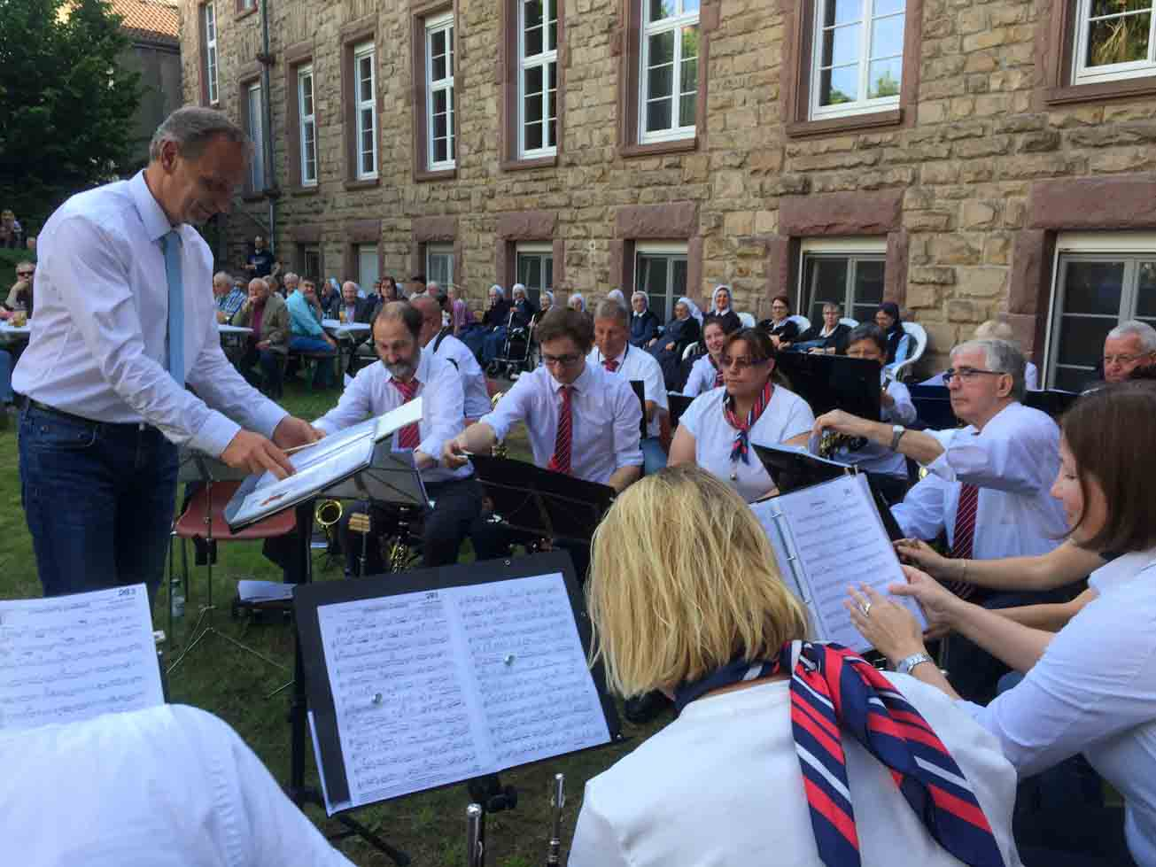 Im Vordergrund die Musiker der Stadtkapelle Heppenheim in weißen Hemden und Blusen, die Männer mit rotblauen Krawatten, die Frauen mit rotblauen Halstüchern. Im Hintergrund sitzen die Zuhörer auf Bänken und Stühlen vor dem Westflügel des Klostergebäudes.