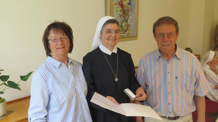 Schwester Brigitta überreicht Gärtnermeister Ernst Sudheimer die silberne Ehrennadel des Caritasverbandes. Links im Bild steht seine Ehefrau Anita.