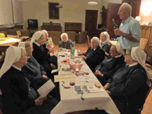 Die Schwestern des Sankt Vinzenklosters in fröhlicher Runde während der Weinprobe im Refektorium des Mutterhauses. Zum Wein werden Wasser und Brot gereicht, das sich auf dem Tisch befindet, andem die Schwestern sitzen. Rechts im Bild steht der Winzer Hans Engelhard mit einer Flasche Wein.