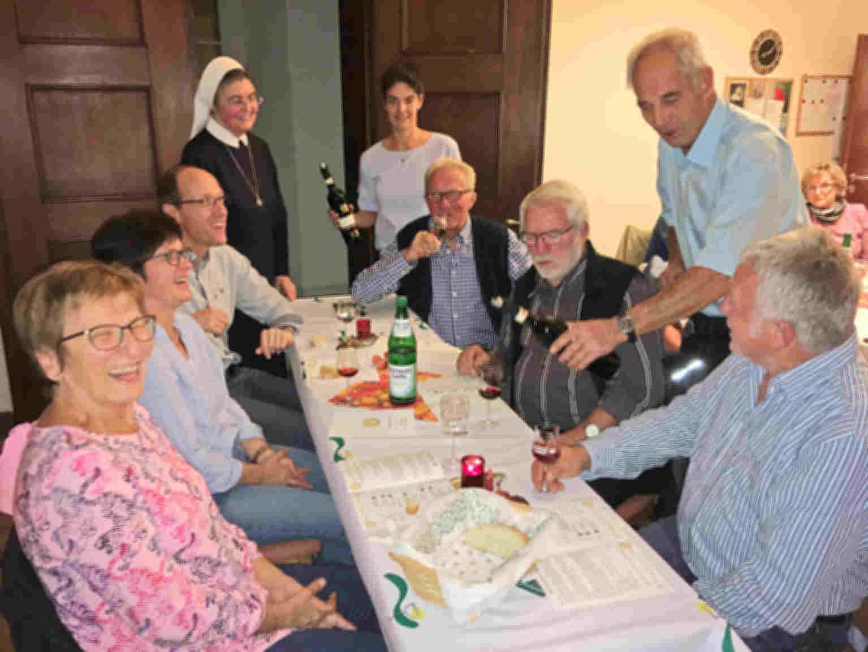Gäste sitzen am Tisch während der Weinprobe im Mutterhaus der Vinzentinerinnen. Stehend am Tisch sind Schwester Brigitta, die ehemalige Weinkönigin Sandra Engelhard und Winzer Hans Engelhard beim Ausschenken des Weins zu sehen