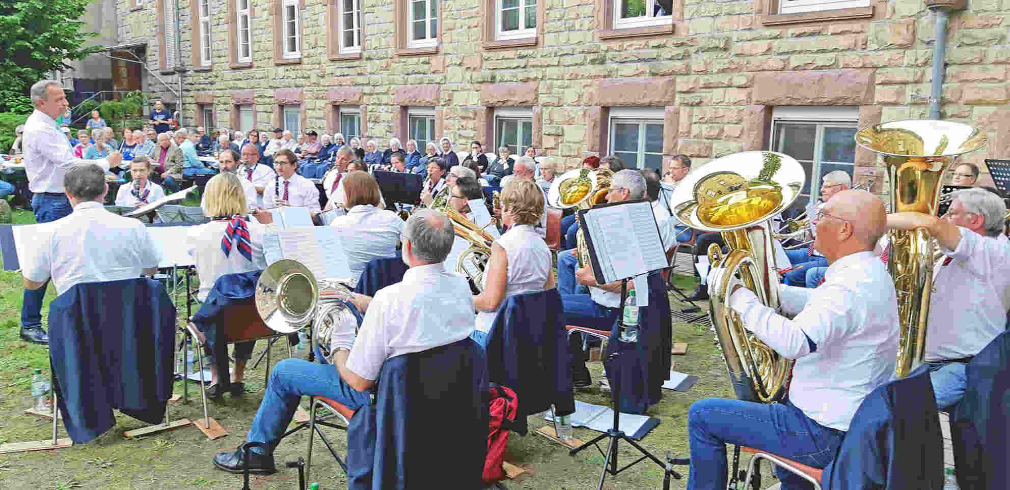 Die Musiker und der Dirigent der Stadtkapelle im Klostergarten der Vinzentinerinnen beim Anstimmen eines Liedes. Vor dem Klostergebäude im Hintergrund sitzen die Gäste und Schwestern auf Stühlen und an Tischen.