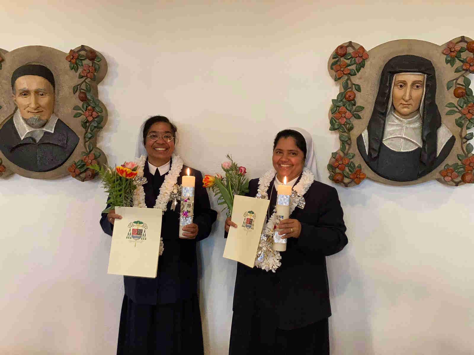 Schwester Elsamma und Schwester Sophy mit Kerzen, Blumen und Urkunde in der Kapelle des Mutterhaus Sankt Vinzenz zum Silbernen Ordensjubiläum. Auf den Seiten befinden sich die Wandilder vom heiligen Vinzenz von Paul und von der heiligen Mutter Luise.
