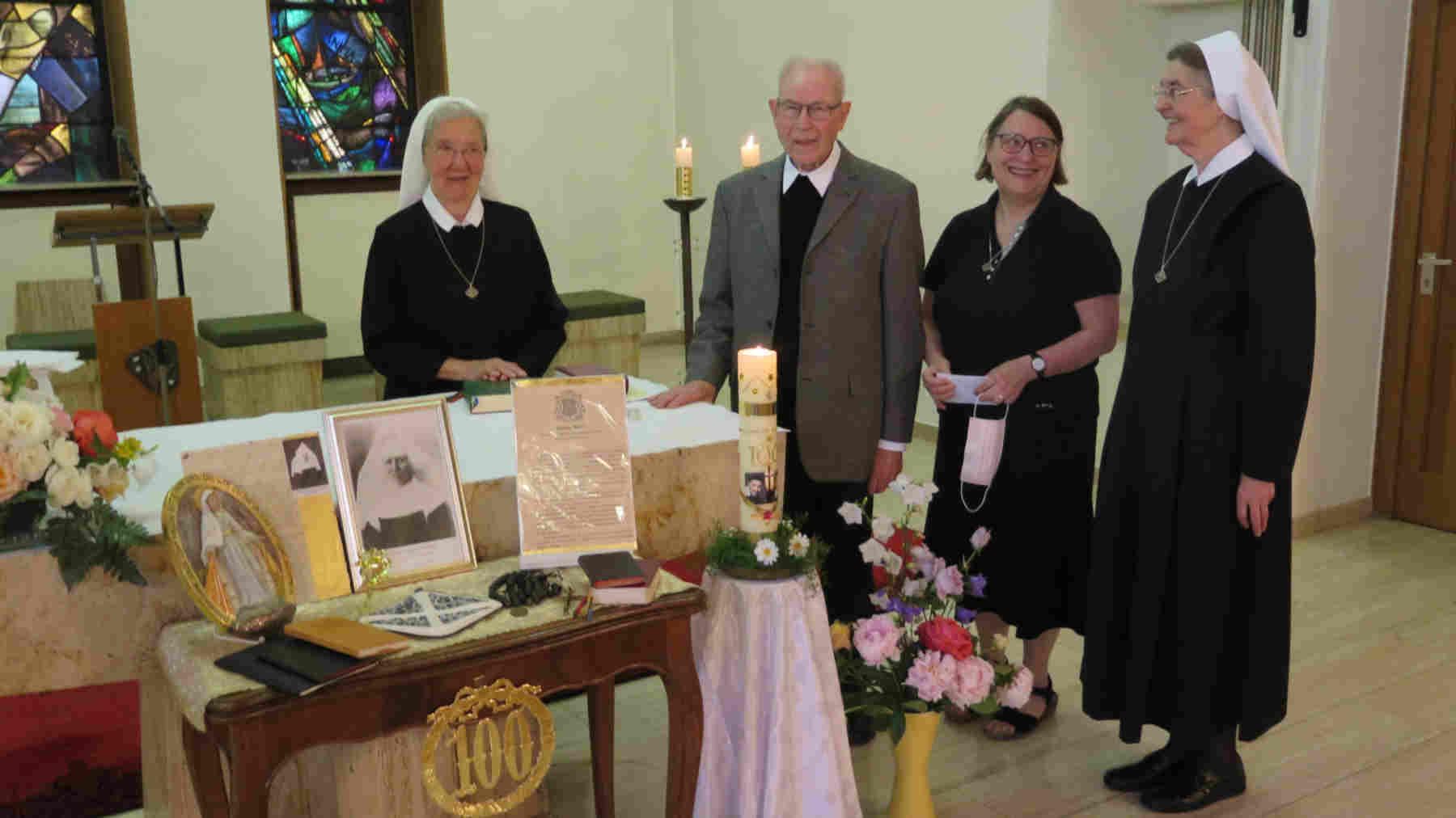 3 Schwestern der Vinzentinerinnen und ein Priester hinter und seitlich am geschmückten Altar der Kapelle der Vinzentinerinnen