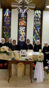 Sieben Schwestern der Vinzentinerinnen stehend hinter dem feierlich geschmückten Altar der Kapelle des Mutterhauses. Im Hintergrund sind die bunten Kirchenfenster des Chorraumes zu sehen, von der Decke hängt ein Kreuz herab.